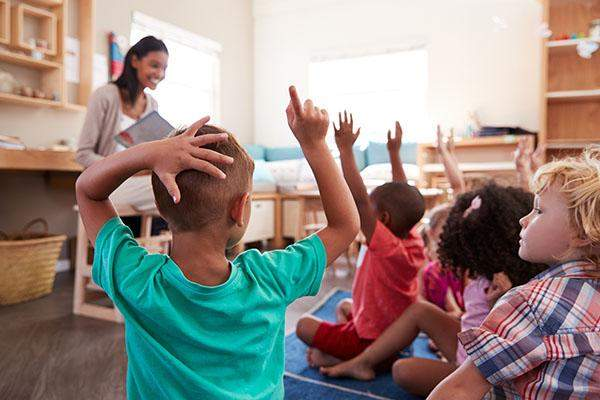 Children in classroom sat in front of teacher, all with their hands up