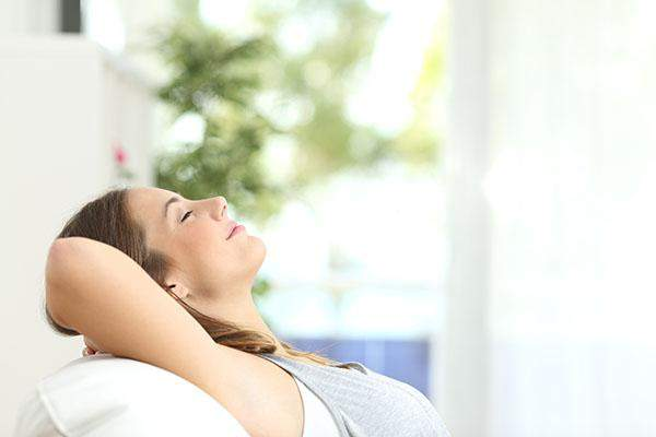 Woman relaxing on safe with arms behind head